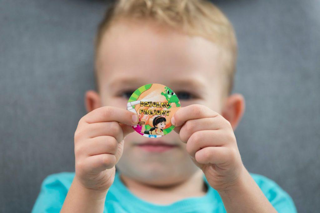 Chłopczyk pokazuje nagrodę po skończeniu zabiegu podologicznego